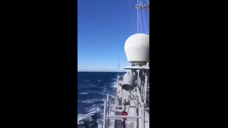 A Turkish F 16 fighter plane flies past a Turkish frigate in the Eastern Mediterranean