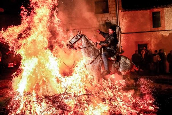 Всадники проезжают через костер испанском городе Сан-Бартоломе-де-Пинарес. Наши дни. Этот ритуал символизирует очищение.