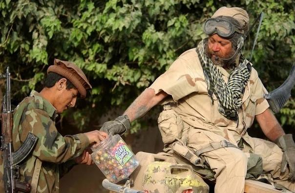 Координатор спецназа армии США делится жевательной резинкой с бойцом ополчения в Северном Афганистане, август 2002 года